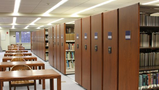 High-density mobile storage condenses book storage to make room for workplaces in public library