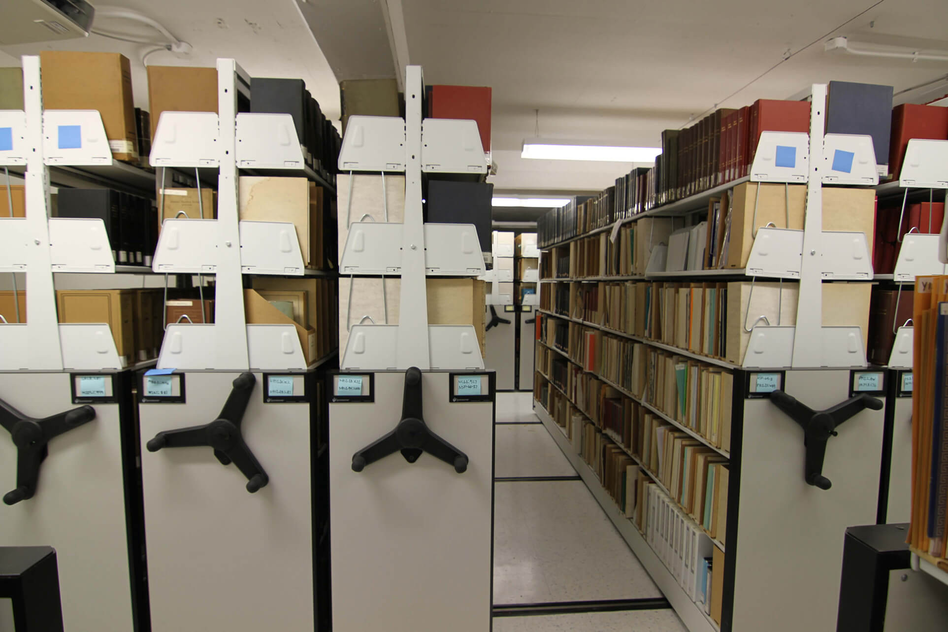 Cantilever library shelving on mechanical assist mobile shelving system
