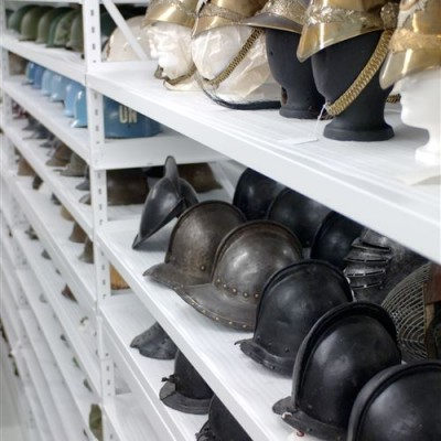 Old military helmets stored on shelving