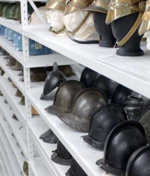 Old military helmets stored on shelving