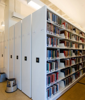 Powered compact mobile shelving for library book storage