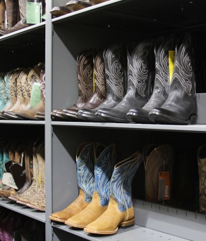 Cowboy Boot storage on static shelving of current and past boot designs